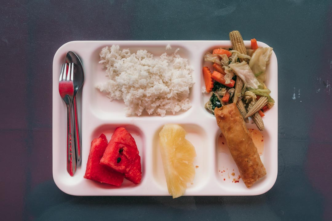 The tray of food from our tour with rice, vegetables, a spring roll and fruit