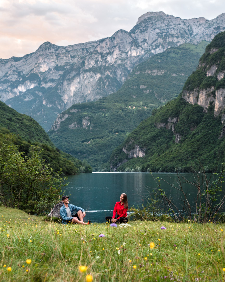 Digital nomad couple Alex & Victoria sitting by the lake in Italy