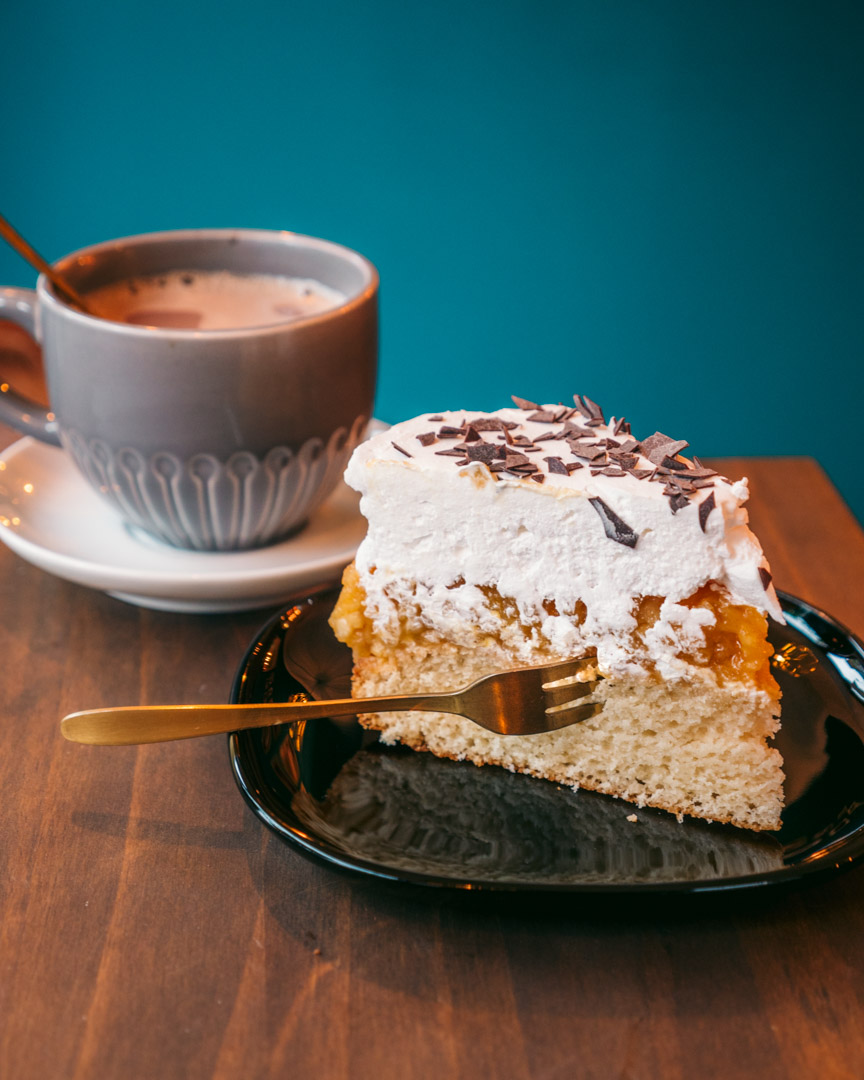 A big piece of apple cake and a delicious hot chocolate in the background