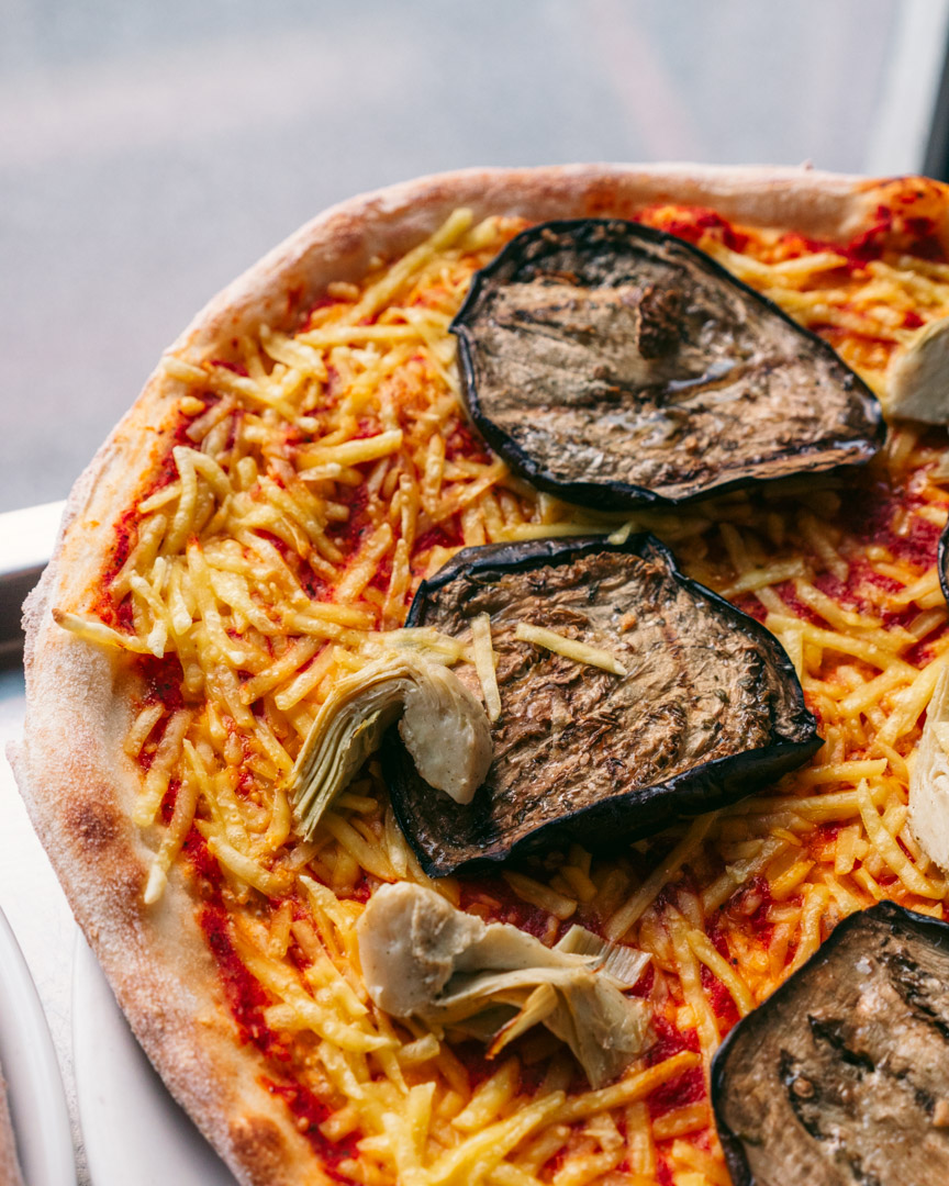 A vegan pizza Margherita with eggplant and artichokes