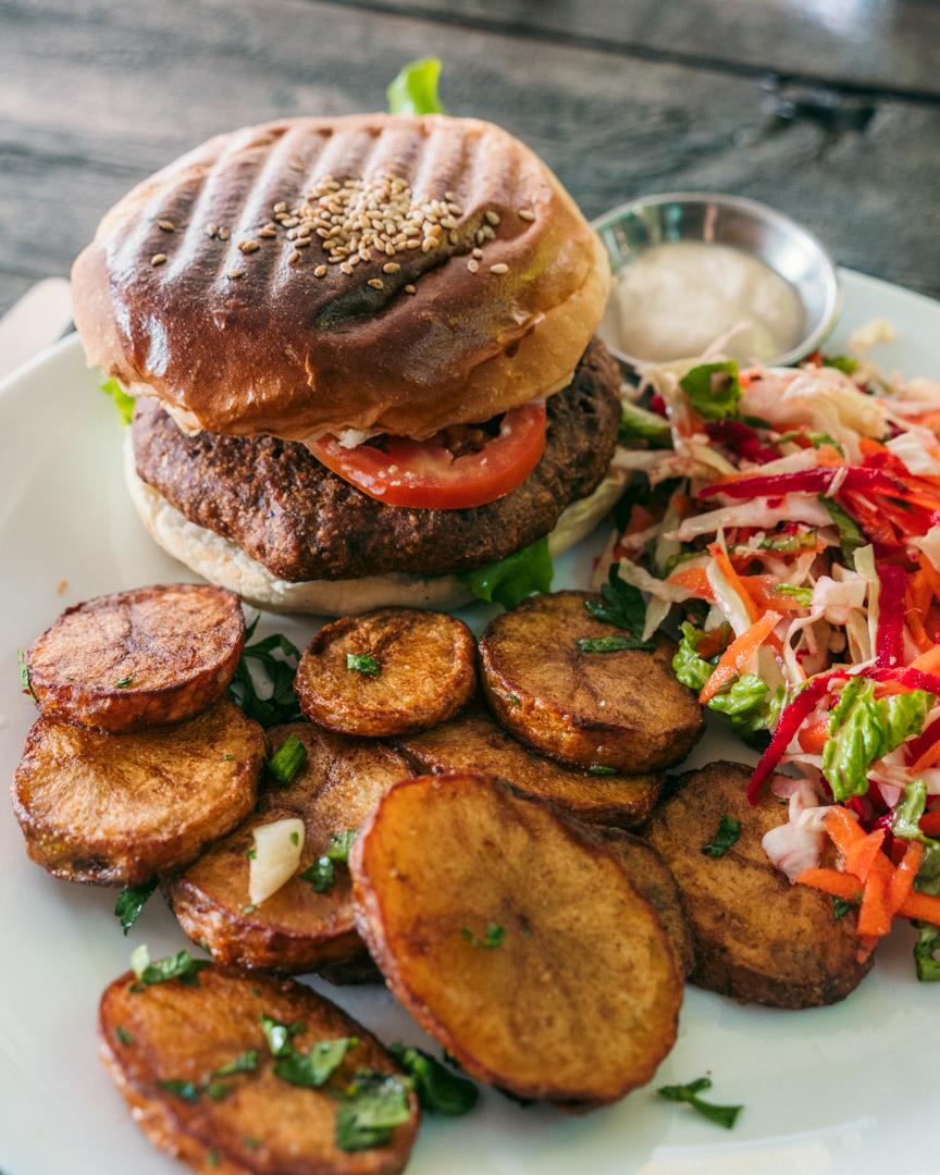 Vegan burger with tofu mayo, slaw-style salad and roasted potatoes.