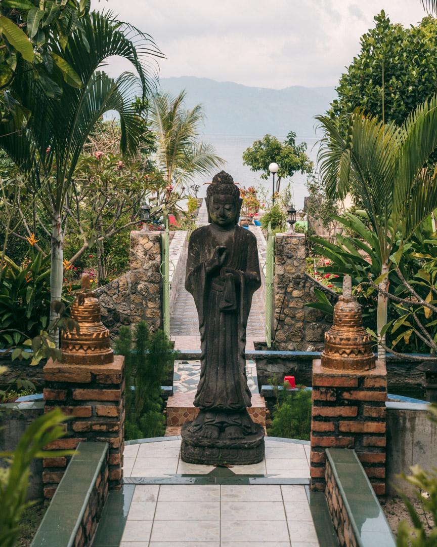 Buddha Café's green garden with statues