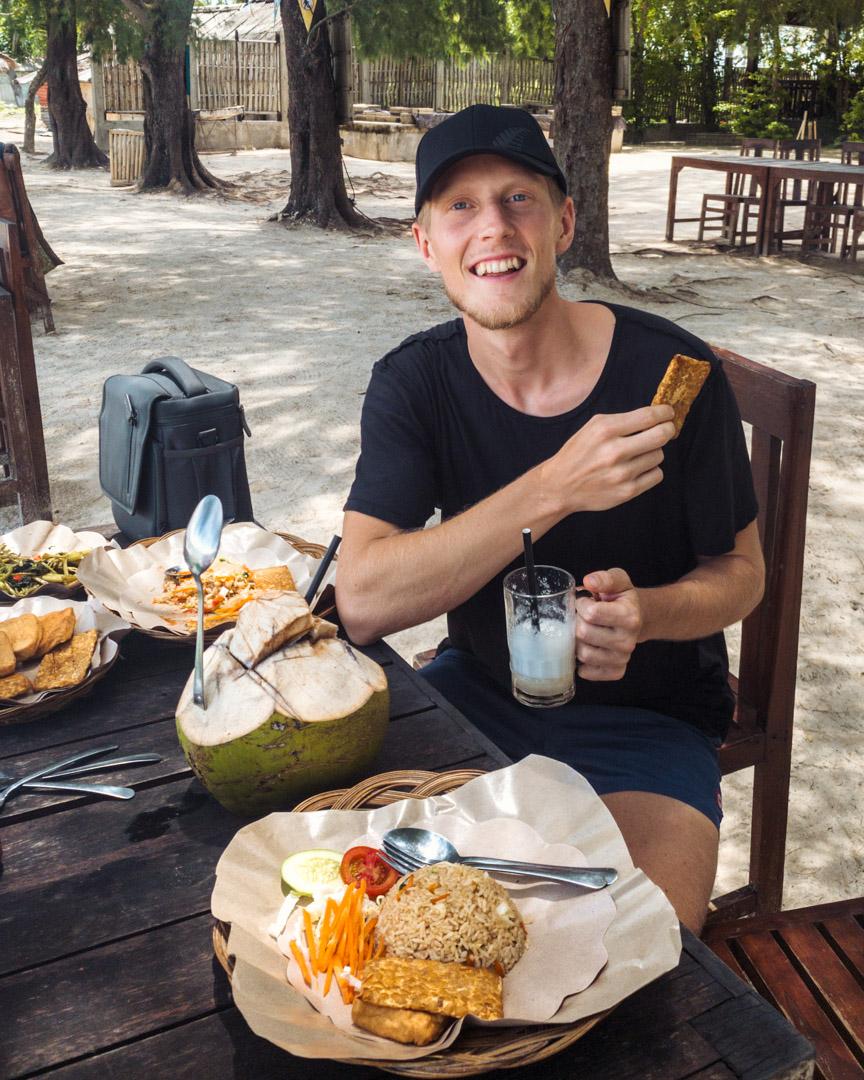 Alex eating food on Gili Sudak Island Lombok Indonesia