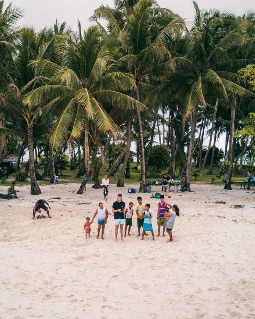 Alex flying the drone with local spectators on Guyam Island