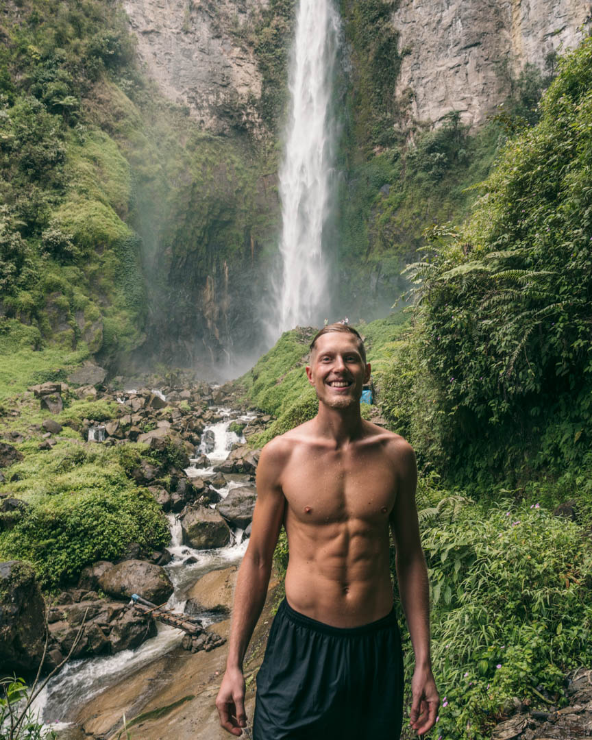 Alex in front of the base of Sipiso Waterfall